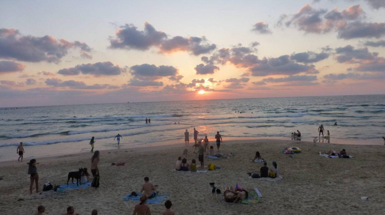 Varias personas disfrutan del atardecer en la playa.