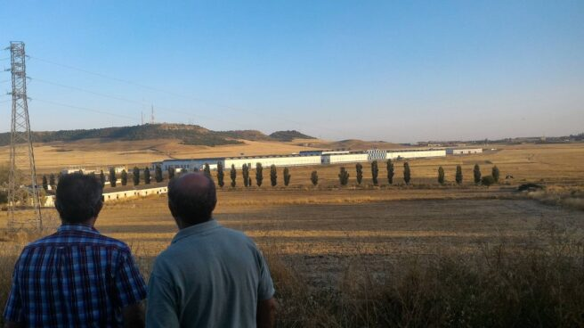 Dos hombres contemplan la Base de Mantenimiento Integral de Renfe desde un alto, en Valladolid.