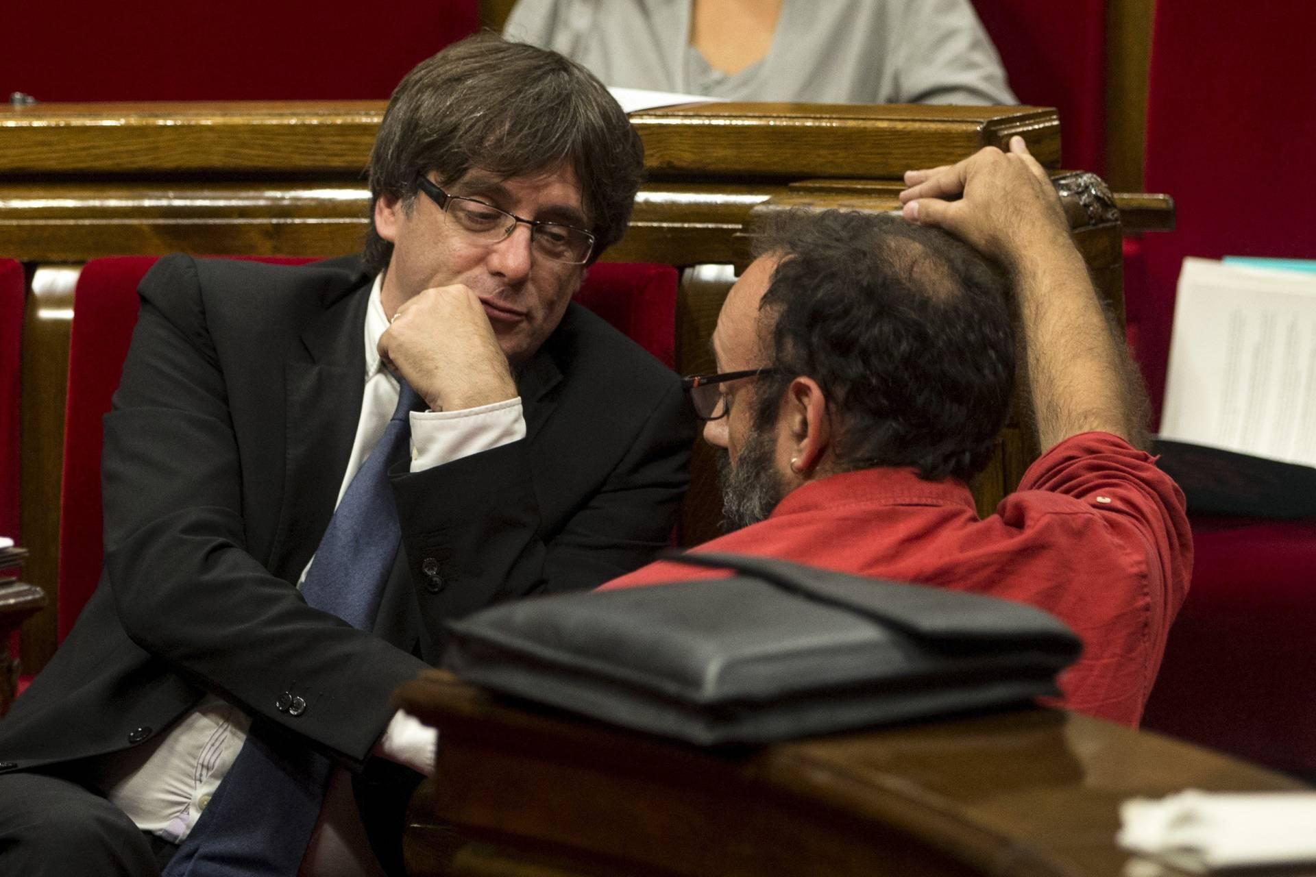 El presidente de la Generalitat, Carles Puigdemont, habla con el diputado de la CUP, Benet Salellas.