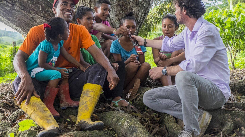 Santiago Peralta (a la dcha.) ofrece chocolate a una familia de campesinos.