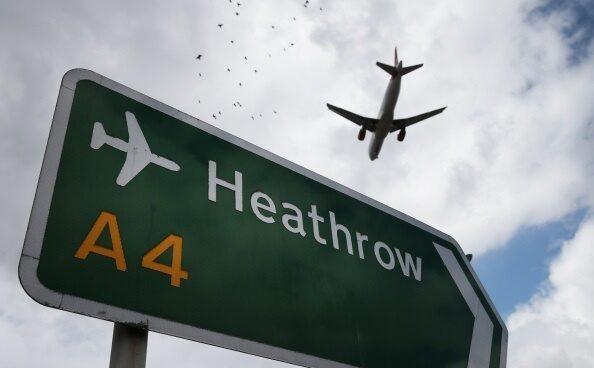 Un avión pasa sobre un indicador del aeropuerto de Heathrow, en Londres.