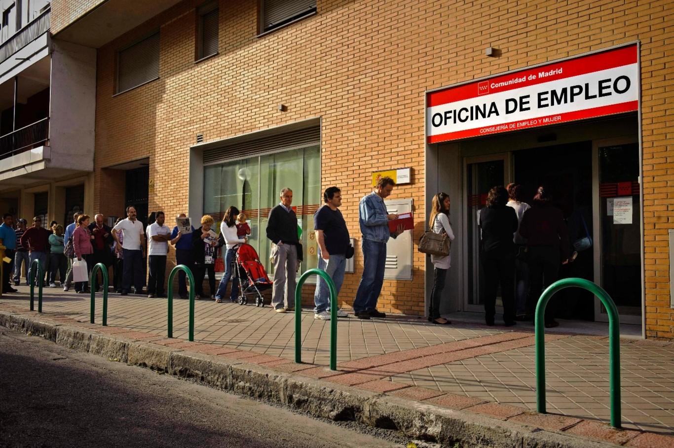 Desempleados españoles hacen cola en una oficina de empleo.