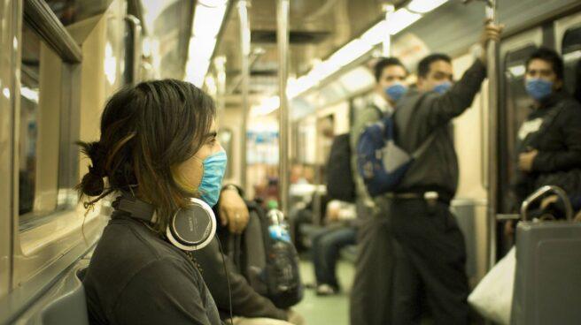 Los pasajeros viajan en el metro con mascarilla para evitar el contagio de la gripe.
