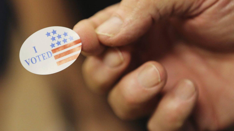 Un voluntario entrega una pegatina a los votantes durante las elecciones presidenciales en un centro electoral de Biloxi, Mississippi. EFE