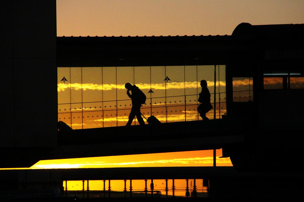Un pasajero en una pasarela de acceso a un avión.