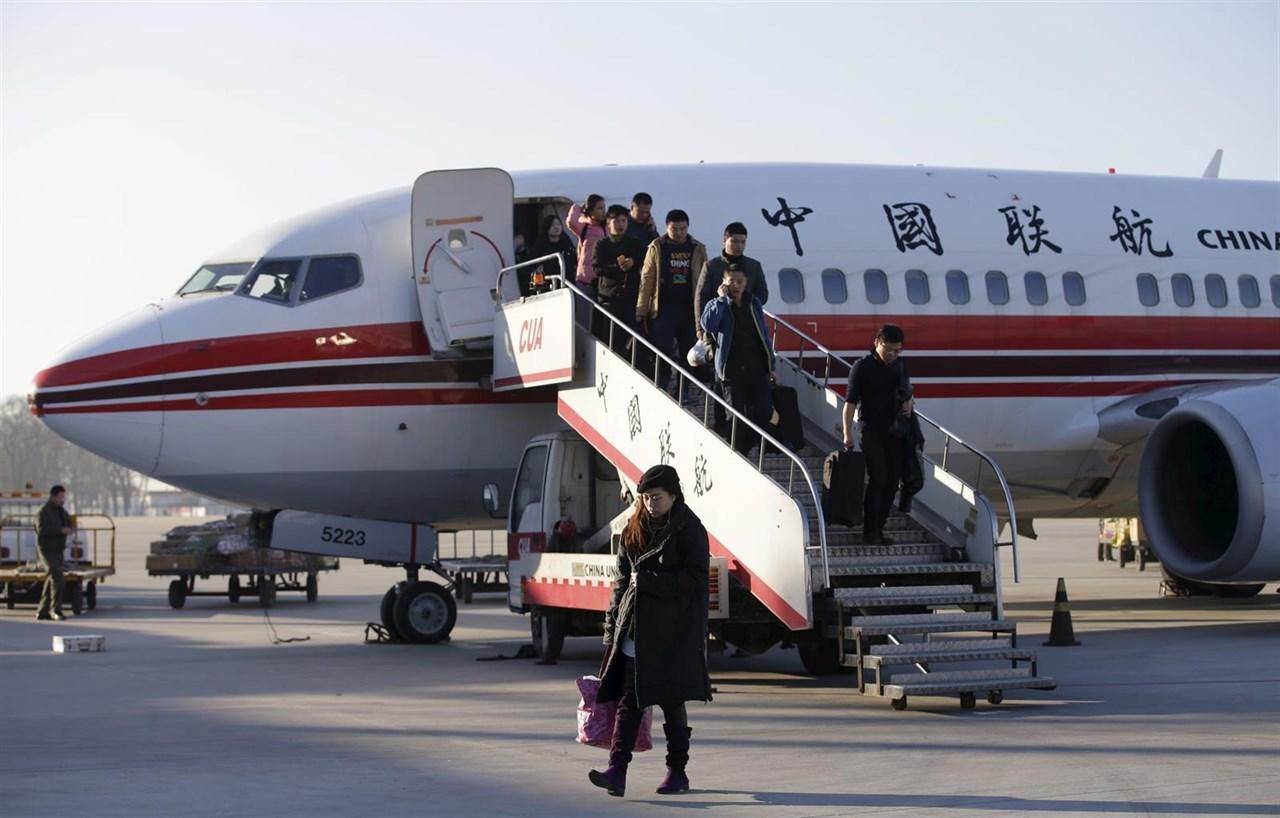 Viajeros descienden de un avión en un aeropuerto de China.