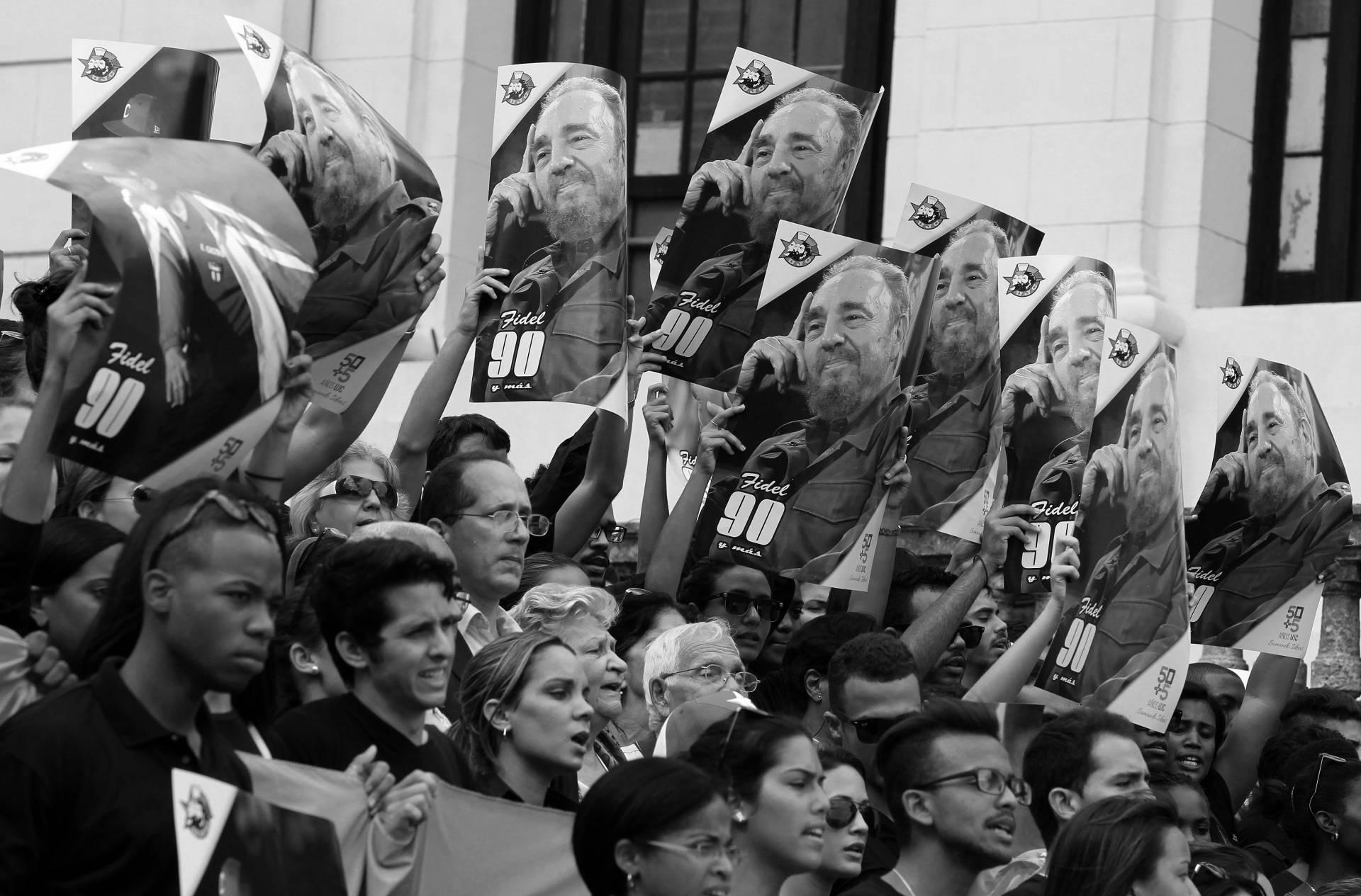 Cientos de cubanos aclaman a Fidel Castro y muestran su imagen en las manos.
