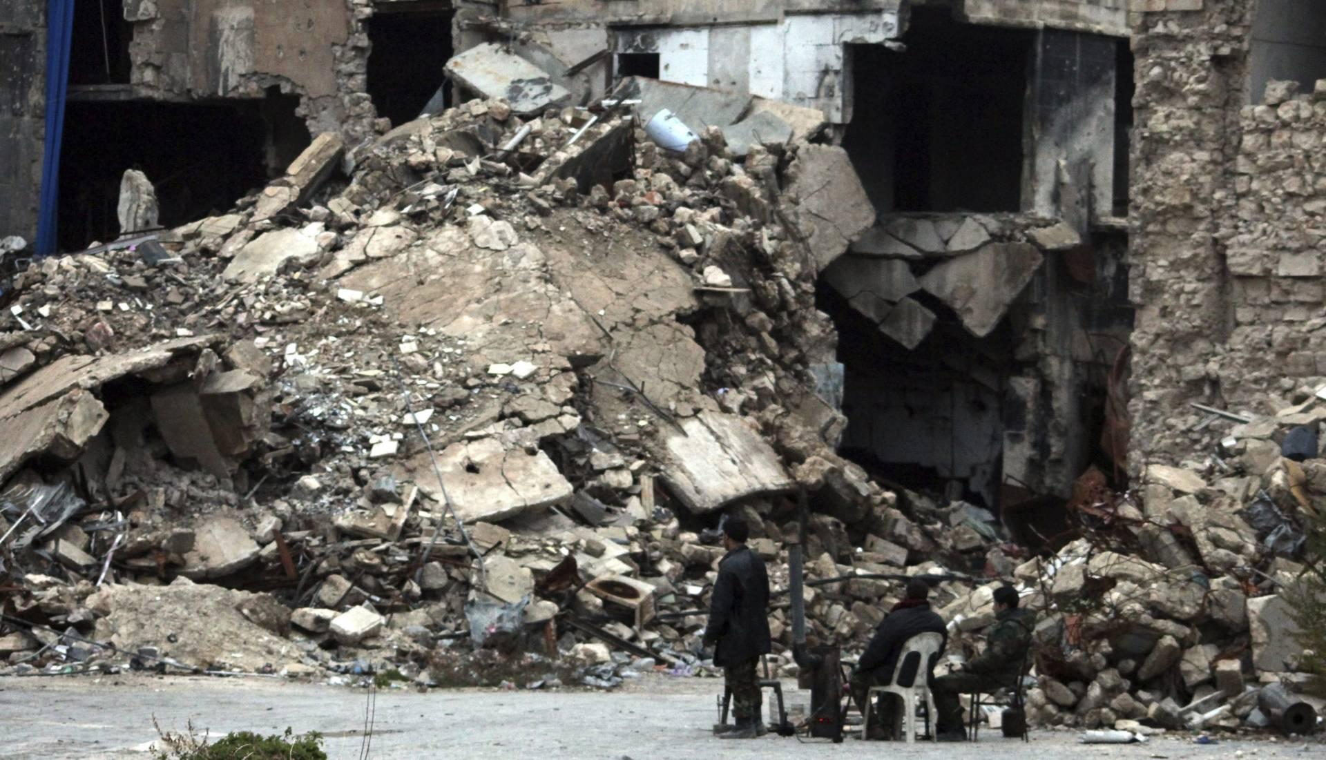Un grupo de personas contemplan un edificio de Alepo en ruinas.