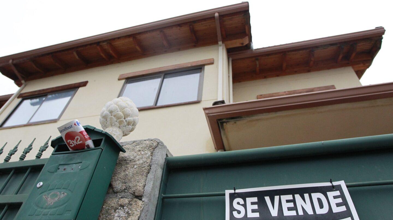 """Una vivienda con un cartel de """"se vende"""" en su fachada."""