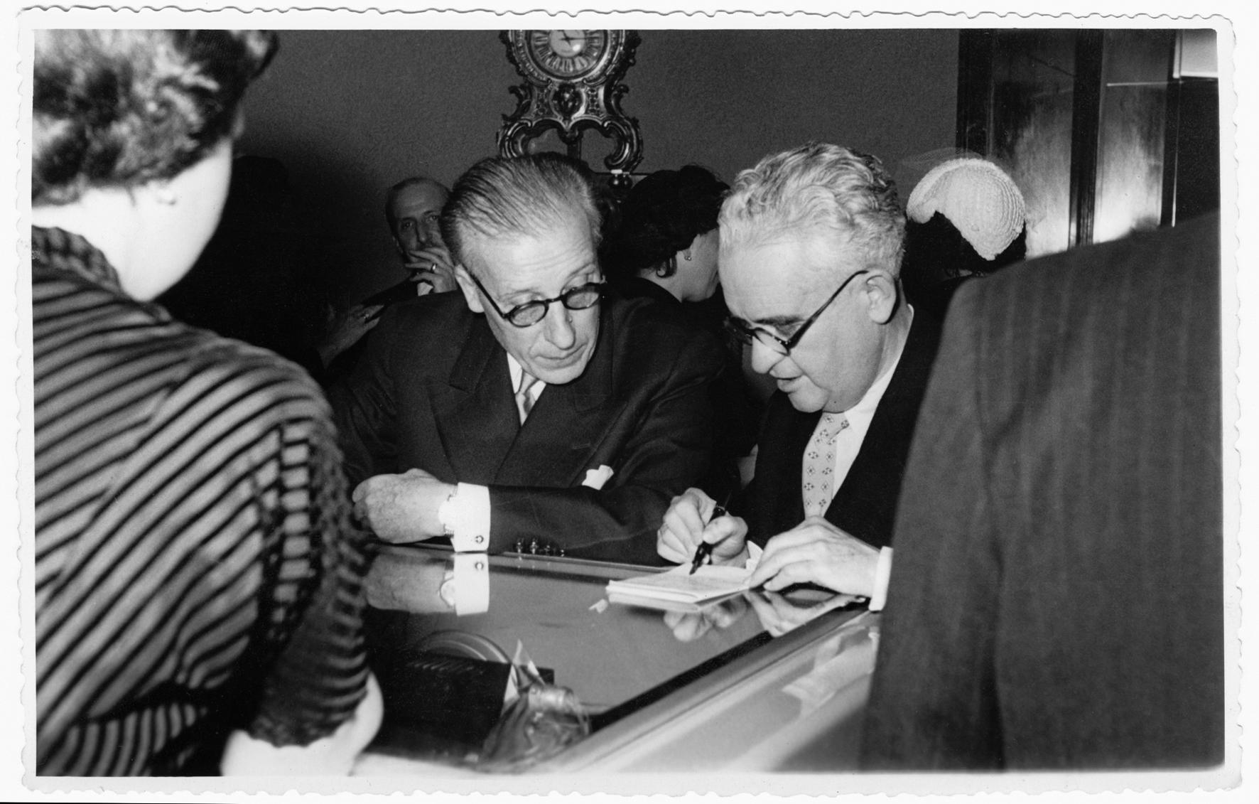 Alejandro Grassy y el ingeniero André Thomas Belin, antiguos compañeros de la Resistencia francesa, apoyados sobre el reloj parlante el día de la inauguración de Grassy (7 de mayo de 1953).