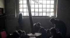 Refugiados de Afghanistan se calientan con un tambor de aceite en un almacén abandonado en Belgrado, Serbia.