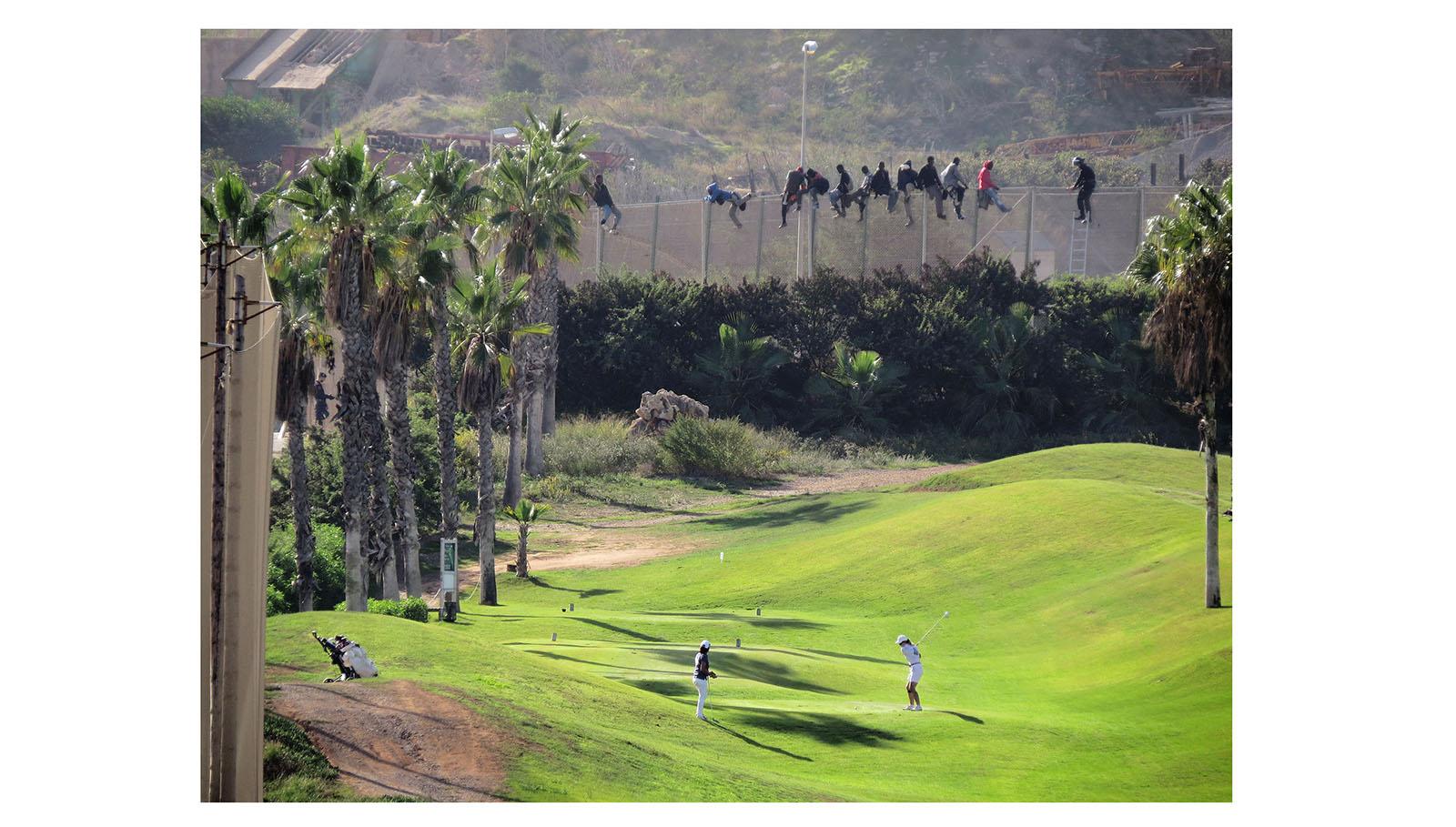 l 22 de octubre de 2014 un grupo de inmigrantes resiste sobre la valla de Melilla, mientras un agente de las fuerzas de seguridad intenta que desciendan. En frente y simultáneamente, dos jugadoras continúan su partido en un campo de golf situado junto a la frontera y pagado con fondos europeos.