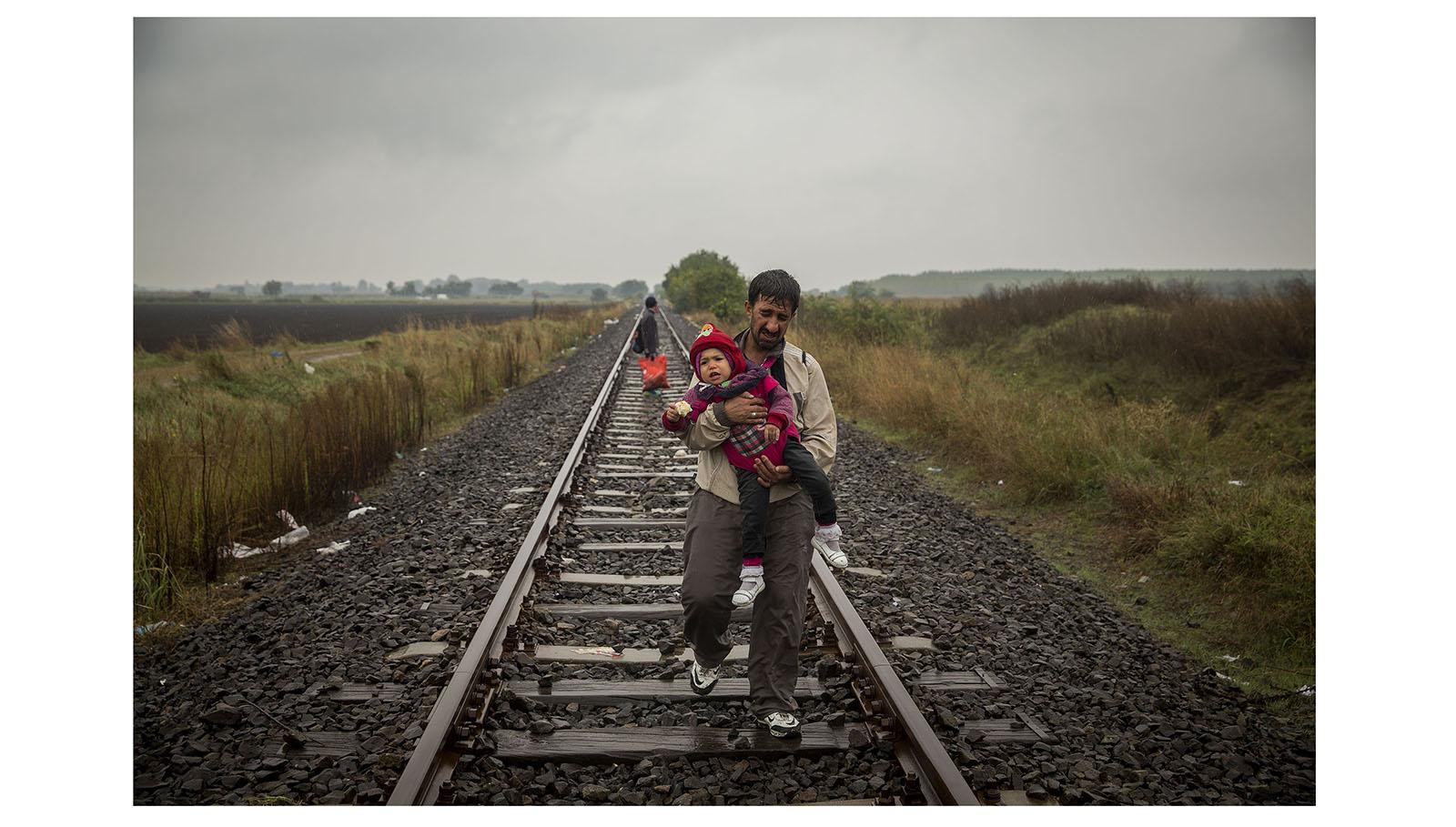 Olmo Calvo. Supervivientes en busca de refugio. 2015-2016 Miles de personas procedentes de países como Siria, Irak o Afganistán abandonaron sus casas huyendo del horror de la guerra, buscando un refugio en Europa donde reanudar su vida. Un periplo en el que familias enteras caminan durante días, viajan en botes hinchables y trenes, aferradas a sus mochilas como únicas pertenencias.