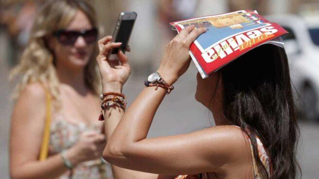 Una turista consulta su teléfono mientras se protege del sol en Sevilla.