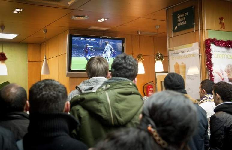 Un grupo de gente ve un partido de fútbol en la televisión de un bar.