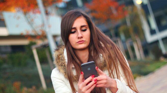 Una joven utiliza su Iphone.