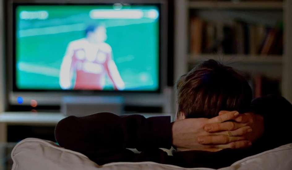 Un espectador ve un partido de fútbol a través de su televisión.