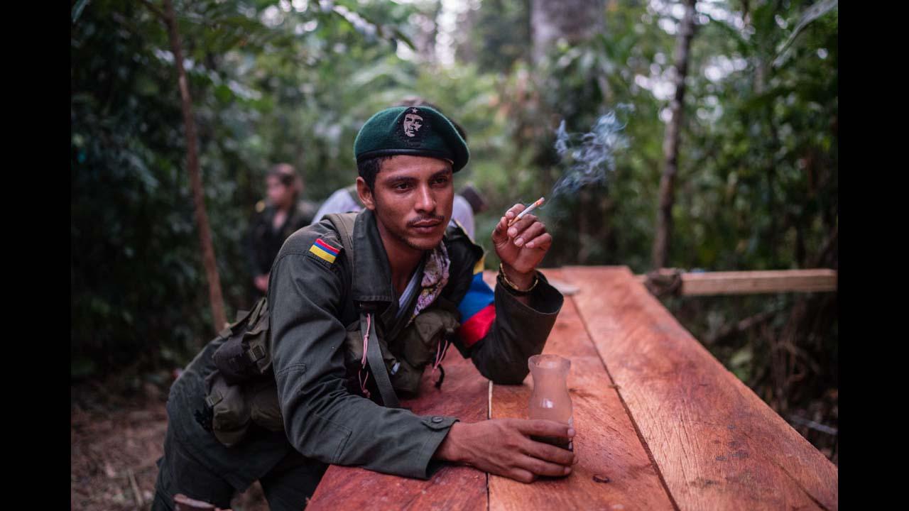 Un miembro de las FARC fumando un cigarrillo con su primer café de la mañana, en la profunda selva colombiana. Federico Rios / ©Native Agency.