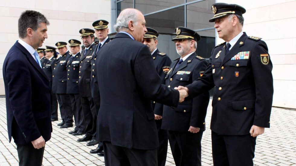 Jorge Fernández Díaz, entonces ministro del Interior, estrecha la mano a Eugenio Pino en presencia de Ignacio Cosidó en un acto de la Policía.