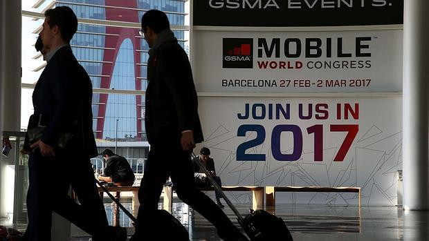 Dos visitantes ante un cartel publicitario del Mobile World Congress.