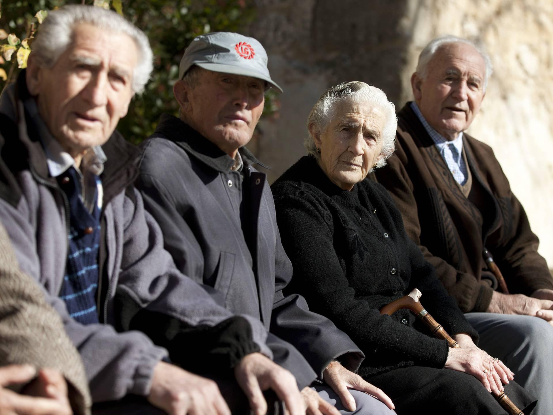 Ancianos sentados en una plaza pública.