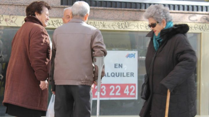 Grupo de personas mayores ante de un cartel de oferta inmobiliaria.