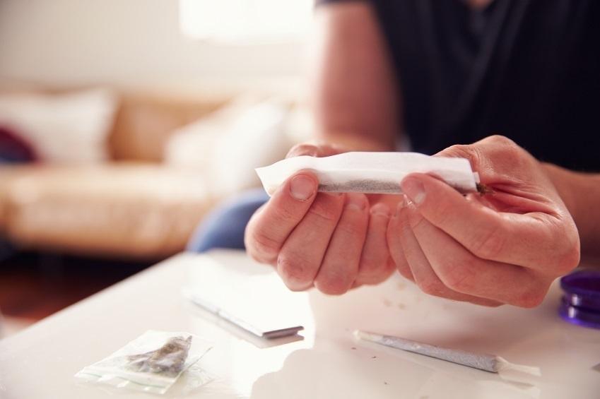 Un joven fabrica un cigarrillo de cannabis.
