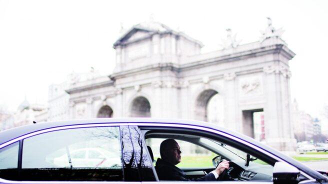 Un coche de Uber, circulando por la Puerta de Alcalá en Madrid.