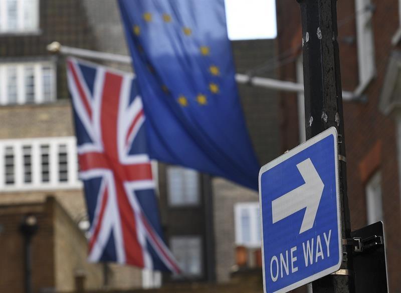 Una bandera europa ondea junto a la británica en una calle de Londres, junto a un indicativo de salida.