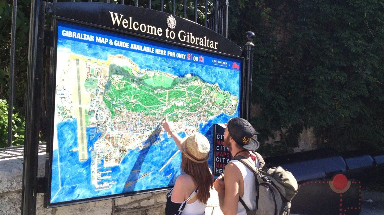 Una pareja de turistas observan el mapa de Gibraltar.