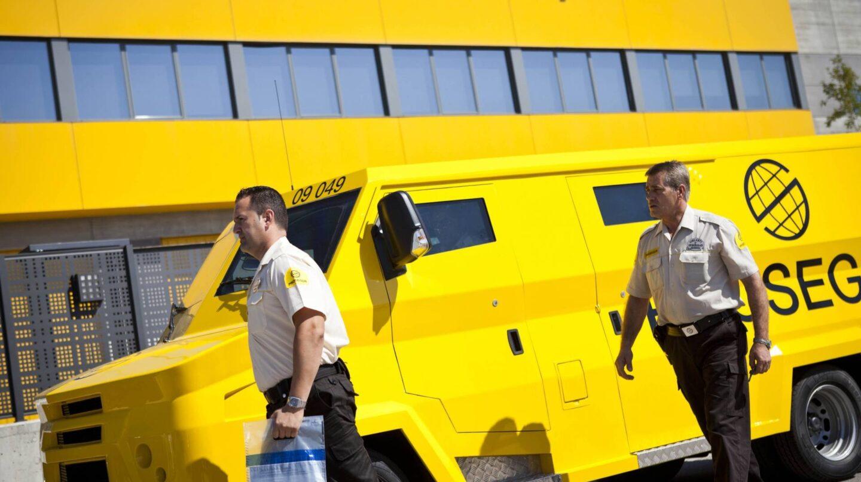 Trabajadores de Prosegur junto a un furgón blindado de la compañía.