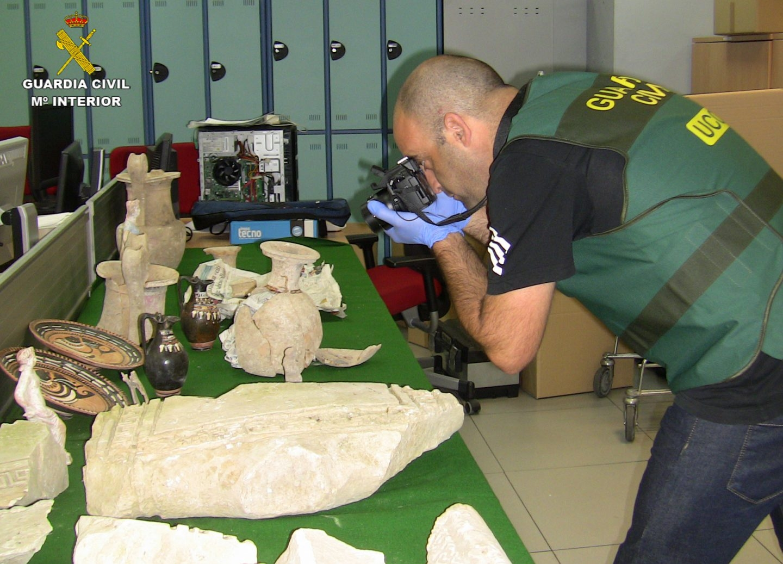 Un agente del Grupo de Patrimonio Histórico de la UCO fotografía piezas recuperadas en uno de los operativos.