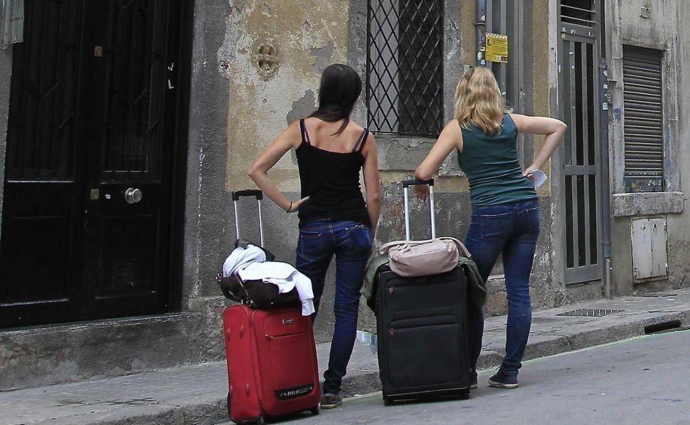Un par de turistas esperan para entrar en un piso turístico.