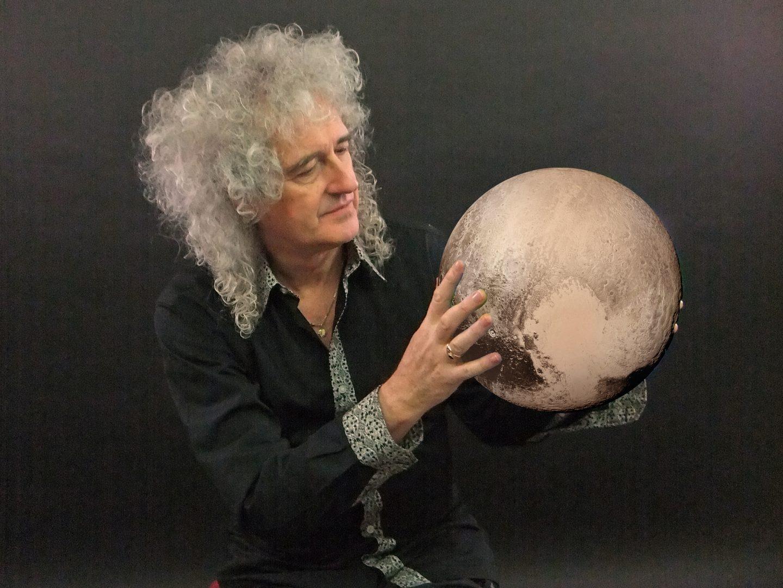 Brian May, guitarrista de Queen y astrofisico, con Plutón