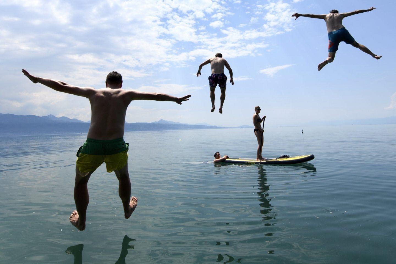 Varias personas disfrutan del buen tiempo en el lago de Lemán en frente de los Alpes.