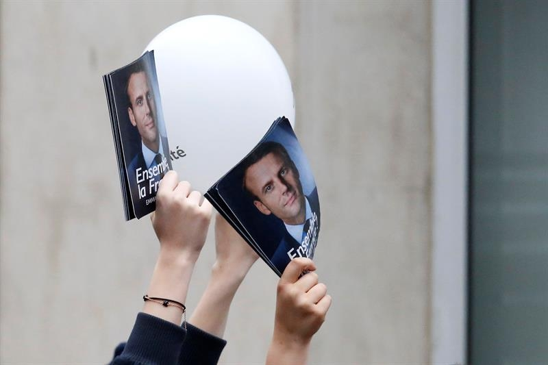 Seguidores de Emmanuel Macron muestran imágenes suyas para celebrar su victoria.