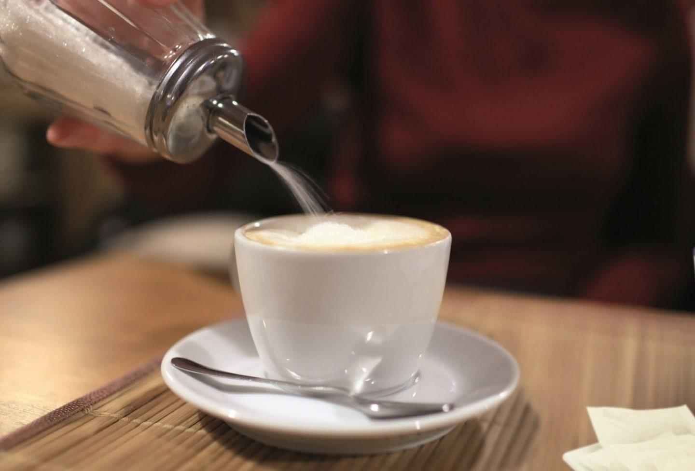 Taza de café con leche y azúcar.