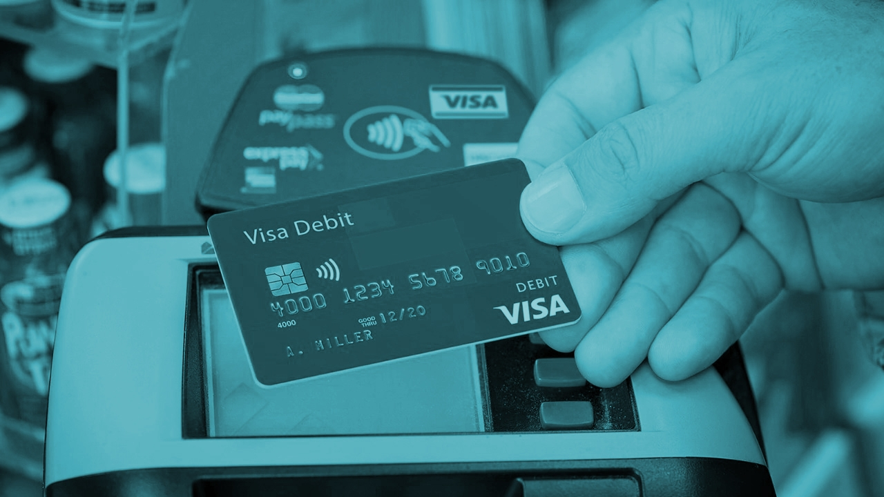Tarjeta de débito y terminal de pago Visa.