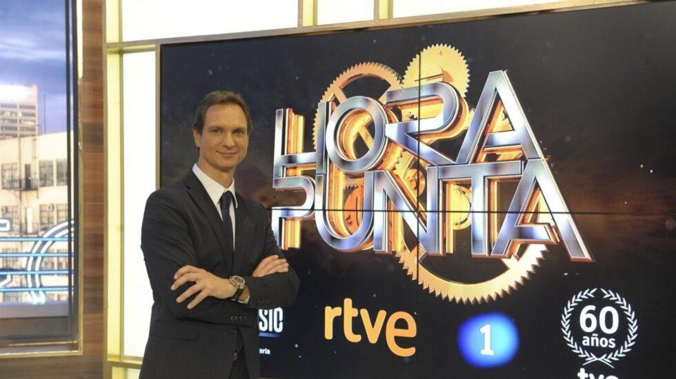 Javier Cárdenas posando frente a la publicidad de Hora Punta
