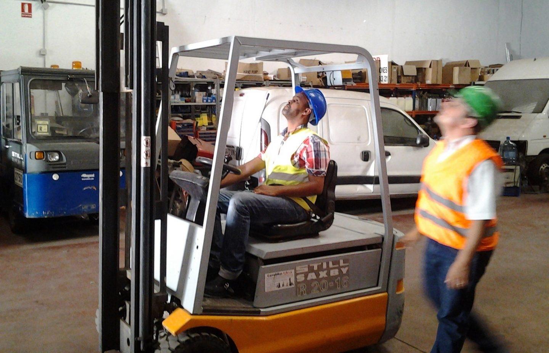 Trabajador aprendiz usando maquinaria en una fábrica de Málaga.