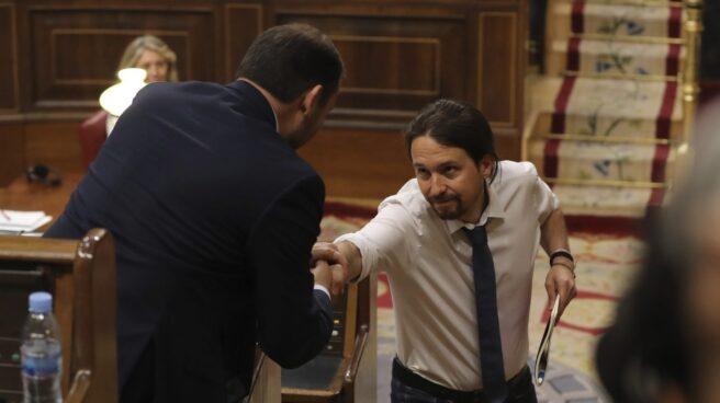 El líder de Podemos, Pablo Iglesias, da la mano al portavoz socialista, José Luis Ábalos, durante el debate.