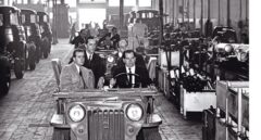 Eduardo Barreiros conduce un coche en su factoría junto al príncipe Juan Carlos.