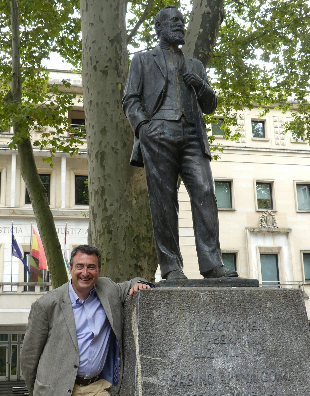 El portavoz del PNV en el Congreso, Aitor Esteban, junto a la estatua en honor de Sabino Arana ubicada ante la sede del PNV.