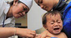 Una enfermera vacuna a un bebé sujetado por su madre en Camboya.