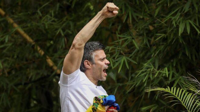 Leopoldo López saluda desde la verja de su casa en Caracas.