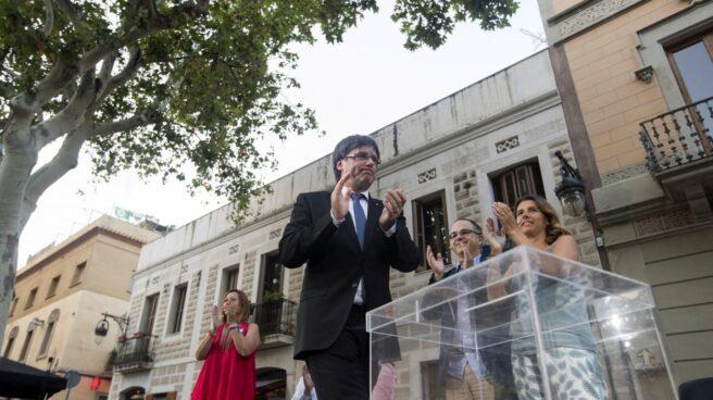 El 'president' de la Generalitat, Carles Puigdemont, junto a una urna simbólica.