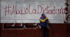 Un opositor hace un descanso junto a un cartel contrario al gobierno de Maduro.