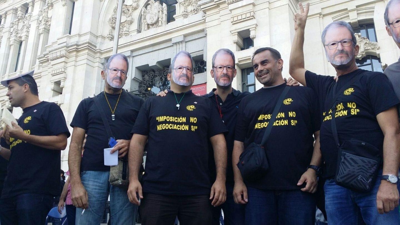 Varios manifestantes con la careta del delegado de Seguridad Javier Barbero.