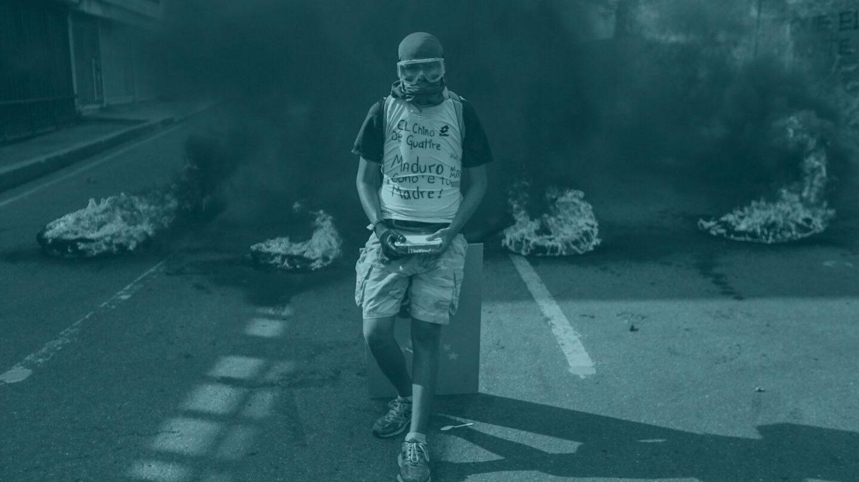 Un manifestante permanece en frente de una barricada en llamas durante una manifestación en Venezuela.