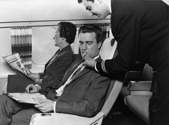 Personal de vuelo de KLM enciende un cigarrillo a un viajero, cuando la aerolínea permitía fumar.
